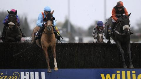 Riders jump a fence at the William Hill King George VI Chase