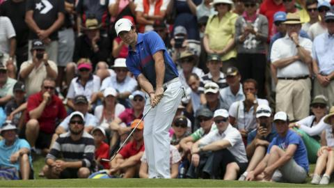 Spectators watch as Northern Ireland's Rory McIlroy hits a chip shot on the second hole during the fourth round of the Australian Open