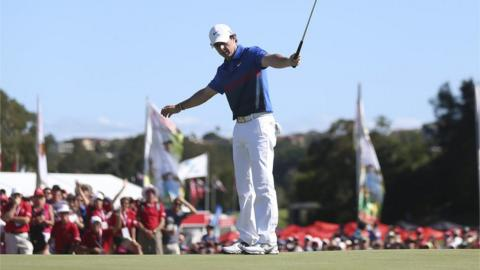 Rory McIlroy holes his birdie putt on the final green to secure a dramatic one-shot victory over Adam Scott at the Australian Open