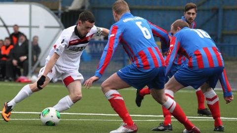 Paul Heatley of Crusaders takes on Ards opponents David Armstrong and Andrew Hunter during the match at Clandeboye Park
