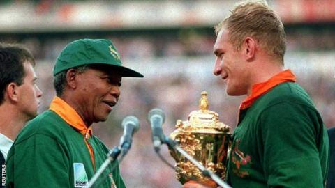 South African President Nelson Mandela (L) presents the William Webb Ellis Cup to Springbok captain Francois Pienaar