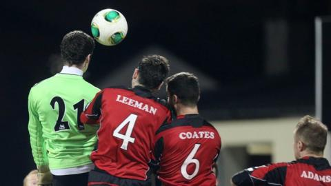 Dungannon Swifts goalkeeper Niall Morgan challenges with three Crusaders players