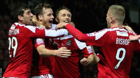 Joe Clarke is mobbed by team-mates after giving Wrexham the lead against Oxford United in the FA Cup at the Racecourse. But the visitors hit back to secure a 2-1 win.