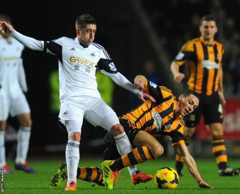 Swansea's Pablo Hernandez battles for possession with Hull City's James Chester.