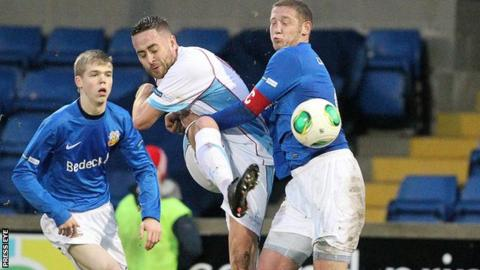 Ballymena striker Shane Dolan is challenged by Glenavon defender Kris Lindsay
