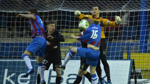 Elliott Morris punches the ball clear at Clandeboye Park as Ards and the Glens play out a goal-less draw