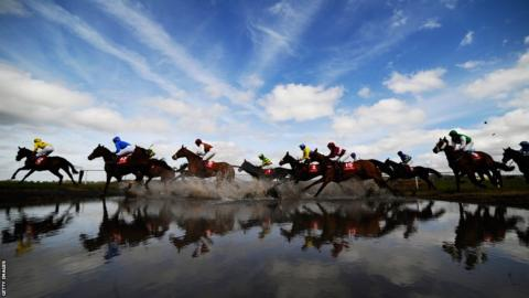 Runners make their way through 'Joe's Water Splash' at Punchestown racecourse in Naas, Ireland.