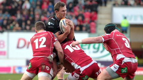 Ospreys centre Ashley Beck runs into fierce defence from Scarlets backs Scott Williams and Rhys Priestland in a full-blooded holiday clash at Parc Y Scarlets