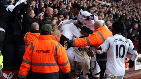 Swansea players and supporters celebrate Roland Lamah's equaliser in the 1-1 draw with Aston Villa at Villa Park.