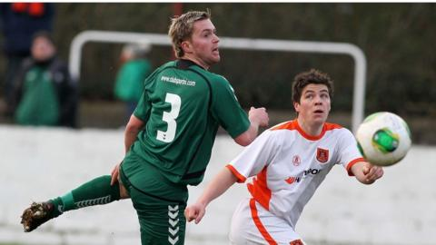 Dundela's Scott Collins challenges for the ball as Carrick Rangers run out 3-2 winners at Taylor's Avenue