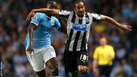 Jonas Gutierrez of Newcastle United holds off a challenge from Yaya Toure of Manchester City