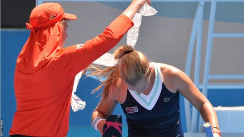 Dominika Cibulkova of Slovakia gets bags of ice around her shoulders to cool off in the heat