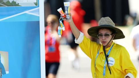 A vendor holds sunscreen as Melbourne heads towards 43C