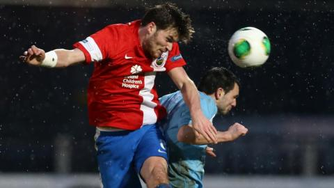 Linfield's Philip Lowry heads in his side's equaliser in the Irish Premiership match against Ballymena United at the Showgrounds
