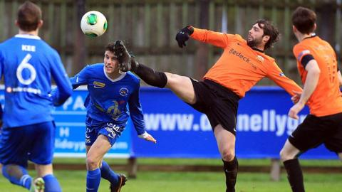 Ballinamallard's Nigel Beacom goes in bravely as Glenavon player-manager Gary Hamilton stretches to reach the ball at Ferney Park