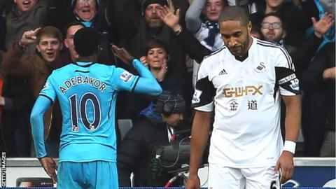 Ashley Williams looks downcast as Emmanuel Adebayor celebrates in front of Tottenham fans