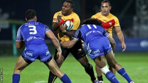 Papua New Guinea's Enoch Maki (centre) is tackled by Samoa's Sia Soliola and Tim Lafai