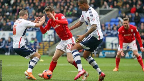 Cardiff City striker Joe Mason is crowded out by two Bolton defenders during the FA Cup fourth round tie at the Reebok Stadium.