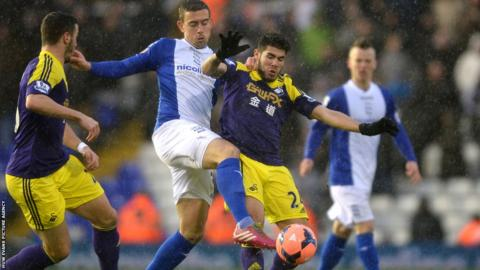Swansea City's Alejandro Pozuelo is tackled by Birmingham City's Olly Lee during the first half of the FA Cup fourth round tie at St Andrew's.