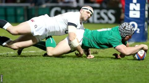 Isaac Boss scores an early try for Ireland despite the tackle of England's Charlie Sharples