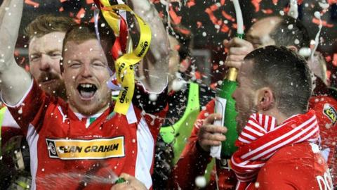 George McMullan lifts the cup after Cliftonville's penalty shot-out win over Crusaders