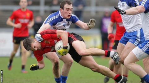 Down's Mark Poland hits the deck under pressure from Padraic Keenan of Monaghan