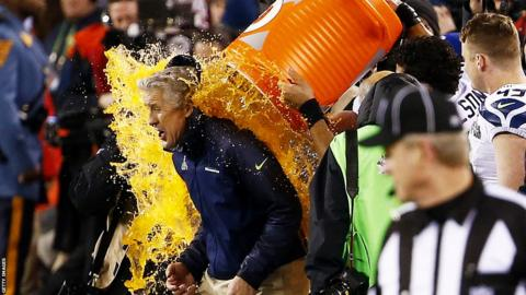 Pete Carroll, head coach of the Seattle Seahawks, is soaked in soft drink as part of the traditional Super Bowl celebrations