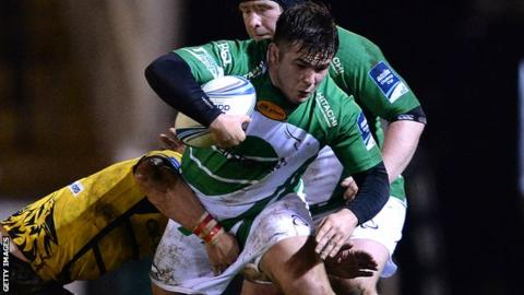George McGuigan (centre) of Newcastle Falcons is tackled by Alexandru Miti of Bucharest Wolves