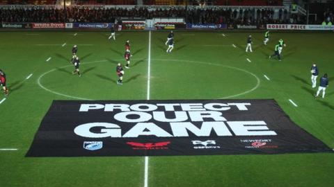 Dragons and Blues players warm up before their match after a protest banner is placed on the pitch