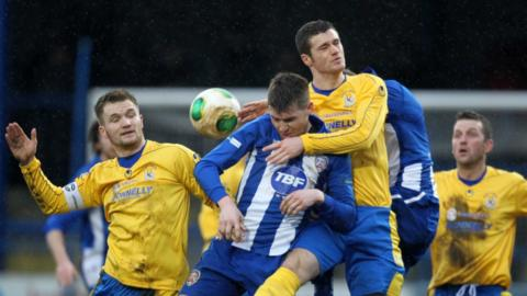 Dungannon duo Ryan Harpur and Gary Liggett in aerial action with Coleraine's Stephen Lowry at Ballycastle Road