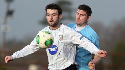 Coleraine's Eoin Bradley holds the ball up as Davy Munster tries to secure possession for Ballymena