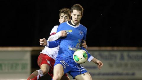 Richard Lecky holds the ball up as David Gibson attempts to gain possession at Ferney Park
