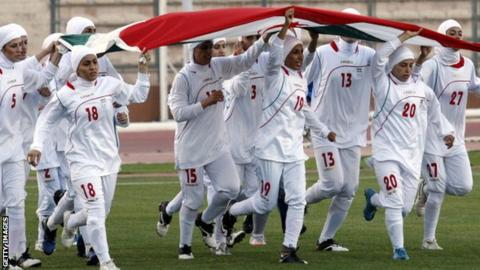 The Iranian women's football team run with their national flag