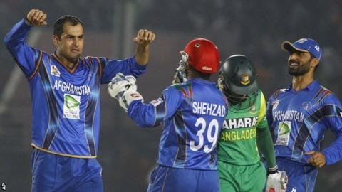 Mohammad Nabi (left) celebrates a wicket