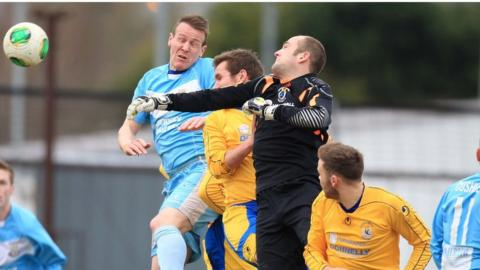 Ballymena captain Allan Jenkins challenges Gareth Buchanan for the ball during the quarter-final at the Showgrounds