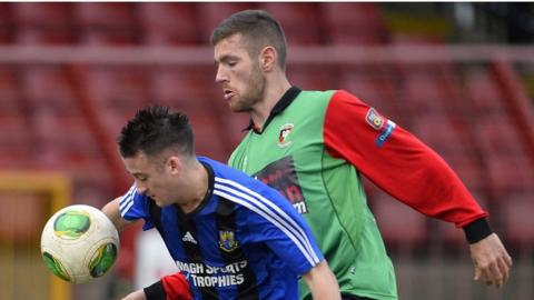 Armagh City's Gareth Grimley shields the ball from Glentoran's Mark Clarke