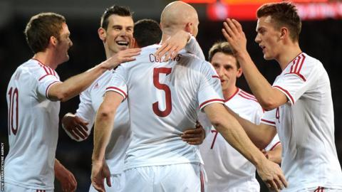 Wales players congratulate defender James Collins after he heads home his country's opening goal against Iceland at the Cardiff City Stadium