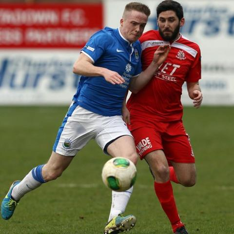 Aaron Burns of Linfield battles for the ball with Sean Mackle of Portadown