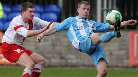 Mark Burns of Ards closes in as Warrenpoint's Liam Bagnall gets the ball away