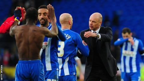 Wigan boss Uwe Rosler and his players celebrate their FA Cup quarter final win at Manchester City