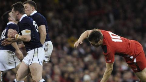 Wales' Dan Biggar is knocked to the floor by Scotland's Stuart Hogg