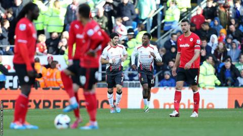 Cardiff City players wait to kick-off for the restart as Luis Suarez celebrates with Daniel Sturridge, who scored Liverpool's fifth goal.