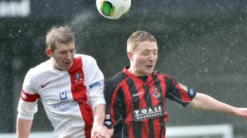 Ross Arthurs of Ards goes up for the ball with Chris Morrow at Seaview where Crusaders came out on top 4-1