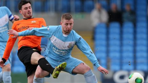 Brian McCaul of Glenavon challenges David Cushley during Ballymena United's 2-1 victory at the Showgrounds