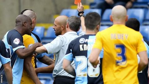 Wycombe players engage with the referee