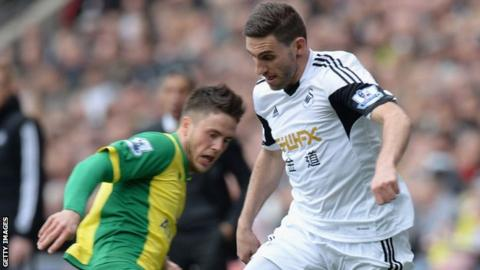 Swansea's Angel Rangel battles for the ball with a Norwich City defender