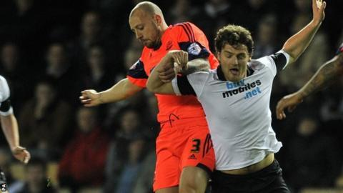 Bolton full-back Alan Hutton (left) challenges Derby striker Chris Martin