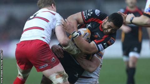Dragons' Taulupe Faletau is tackled by Edinburgh's David Denton and Mike Coman