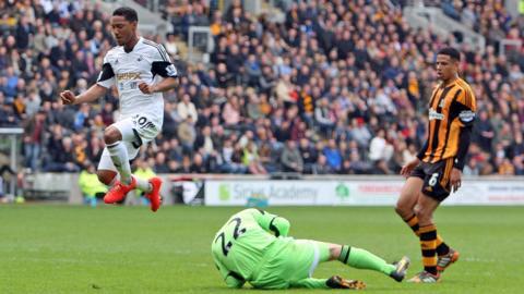 Hull City keeper Steve Harper dives low to deny the advancing Swansea City midfielder Jonathan de Guzman.