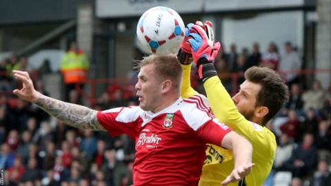 Wrexham striker Andy Bishop and Macclesfield's former Wales Under-21 keeper Rhys Taylor go up for a high ball.